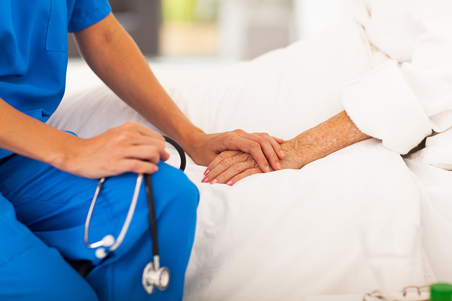 Skilled Nursing Facilities & Long Term Care nurse holding a patients hand